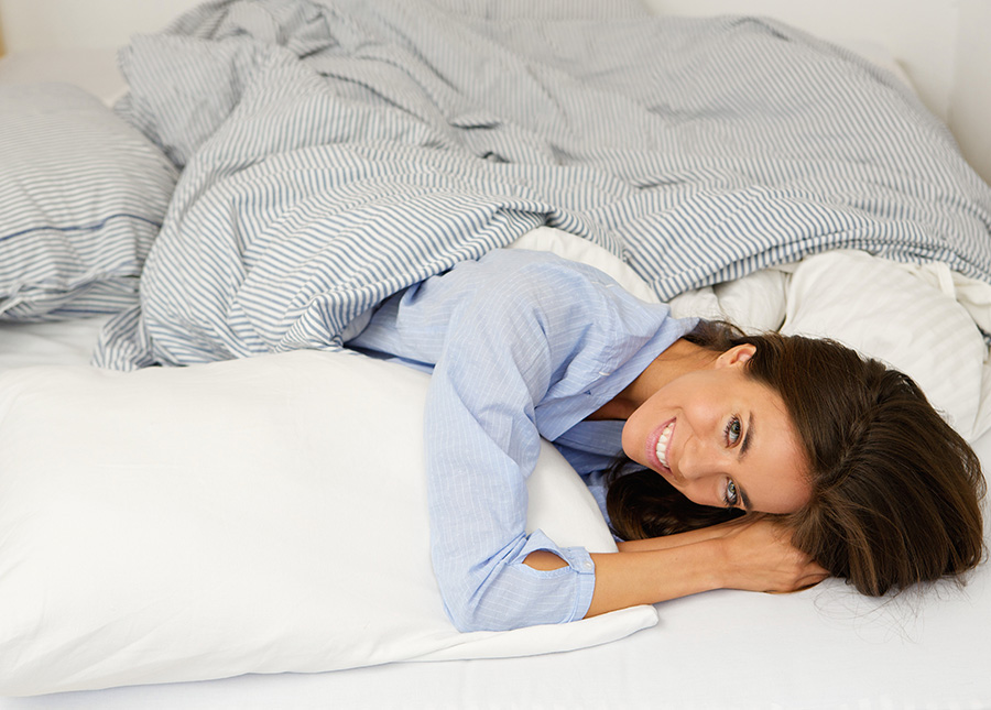 Attractive young woman smiling in bed